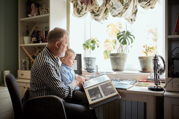 Senior male parent looking at photo memories album with future generation male toddler in front of a window