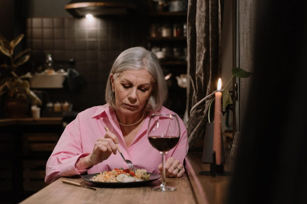 Senior woman in a pink shirt eating a meal with a glass of wine