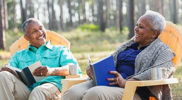 Mature black couple sitting in tan chairs outside laughing and reading books. Wearing a teal shirt and a blue shirt with woods in the background.