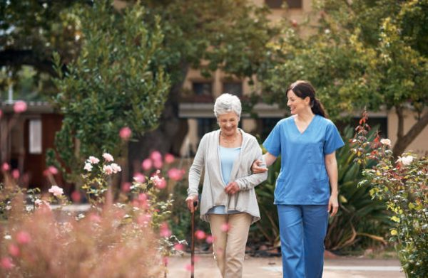 Female healthcare worker wearing blue holding the arm of an elderly lady wearing tan with a cane. Walking through a courtyard with green trees and pink and white flowers